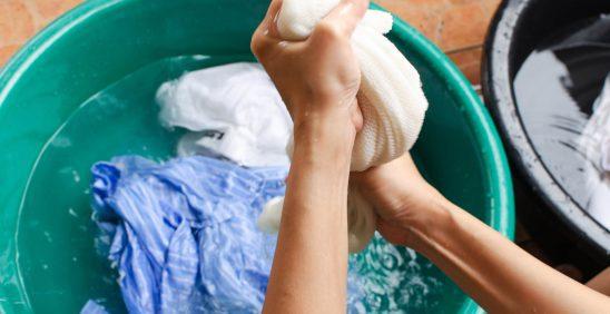 Como remover manchas: Bacia com roupas de molho e pessoa torcendo
