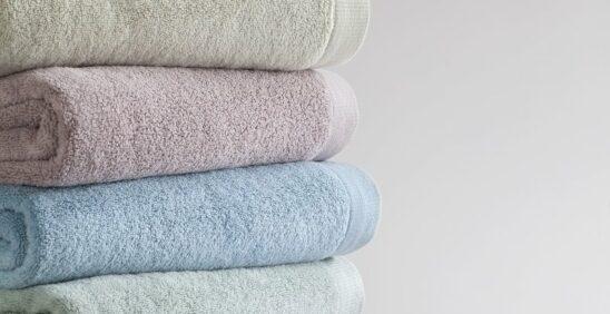 Cinco toalhas Buddemeyer empilhadas em cima de banco de madeira