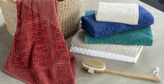 Toalhas Buddemeyer Ambientadas com cesto de palha e escova de banho