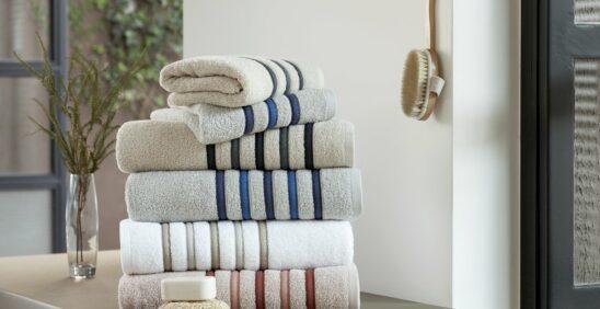 Toalha nova não enxuga? toalhas em cores neutras e claras dobradas e empilhadas em cima de móvel de madeira.
