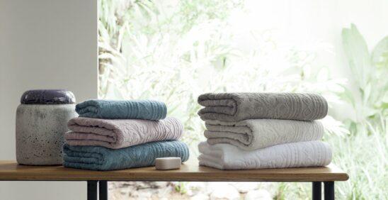 Cuidado com as toalhas: Seis toalhas em cores claras dobradas e empilhadas em cima de banco de madeira