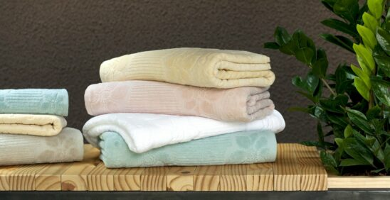 O que é o fio penteado? Sete toalhas em cores claras dobradas e empilhadas em cima de banco de madeira com planta decorativa ao lado