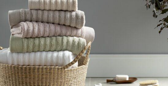 Como organizar roupas no armário Pilha de cinco Toalhas Organic Buddemeyer em cesto de palha
