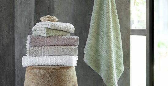 cortar a felpa das toalhasPilha de cinco Toalhas Supreme Buddemeyer em cima de banco